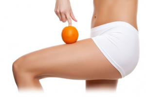Torso of woman in underwear with leg bent holding orange on her leg.