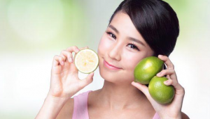 Woman smiling holding limes.