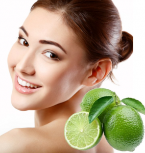 Woman smiling with limes in front of her.