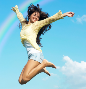 Woman jumping with arms out in the sky with rainbow behind her.
