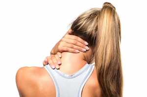 Woman with back to camera rubbing neck and shoulder.