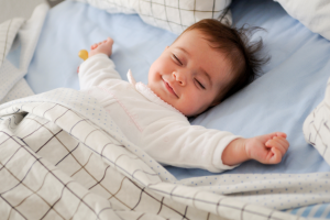 Baby sleeping with arms out to sides.