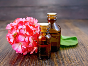 Two small brown bottles next to pink flowers.