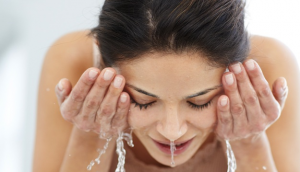 Woman washing face with water.