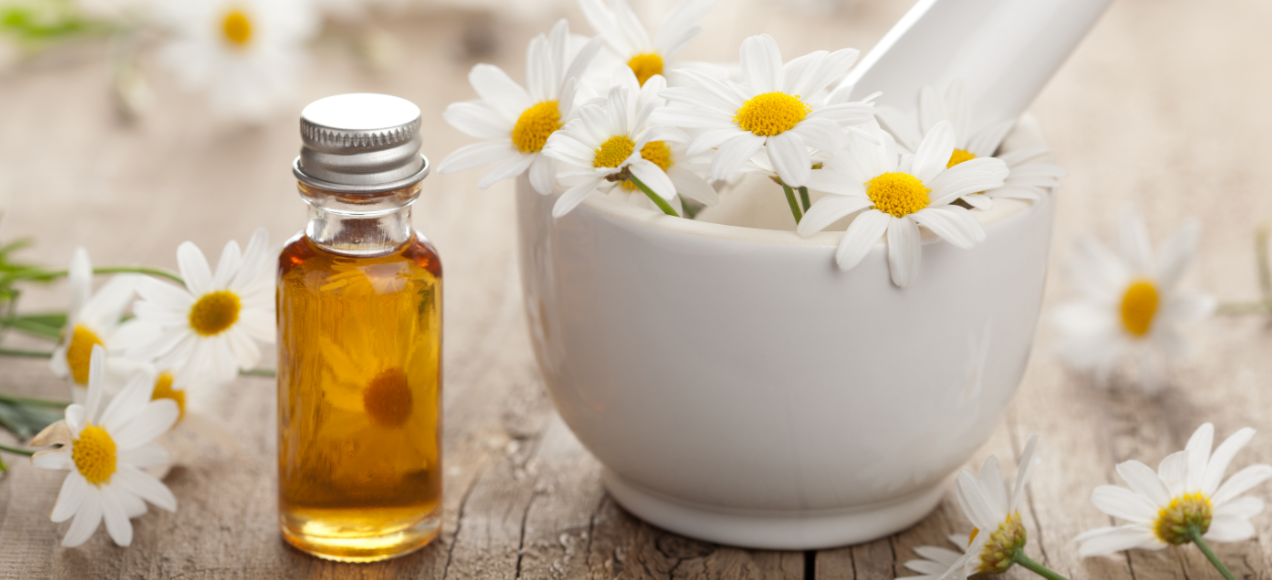 Bowl of chamomile flowers next to small brown bottle.