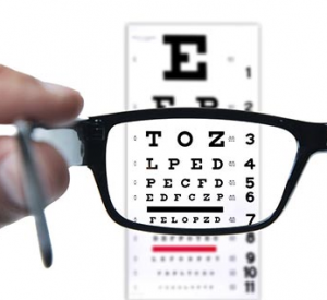 Glasses with alphabet eye chart in background.