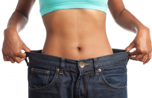 Woman's torso showing weight loss holding jeans out to sides.