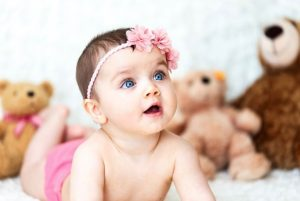 Baby with pink head band lying on stomach looking up with teddy bears in background.