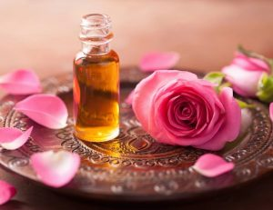 Small bottle of oil surrounded by pink petals and a rose.