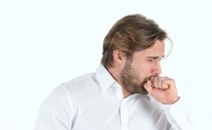 Man coughing into his fist.