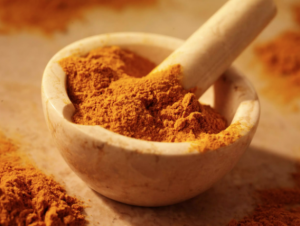 Red powder being mixed in a mortar and pestle.