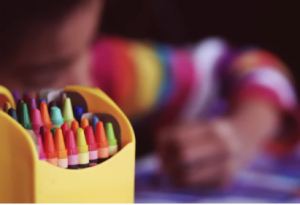 Assorted crayons with child coloring in background.