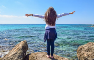 Girl with hands out and back to camera in front of sea.