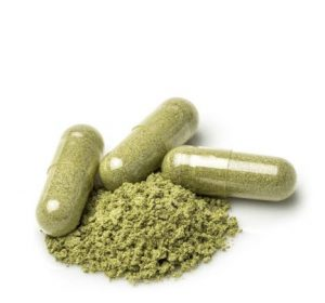 Green pills next to green powder.