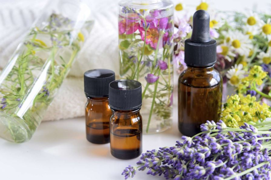 Absolute and essential oils with flowers and herbs.