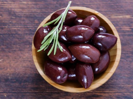 Small wooden bowl full of kalamata olives with a sprig of rosemary on top.
