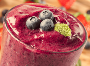 Red smoothie garnished with mint leaves and blueberries.