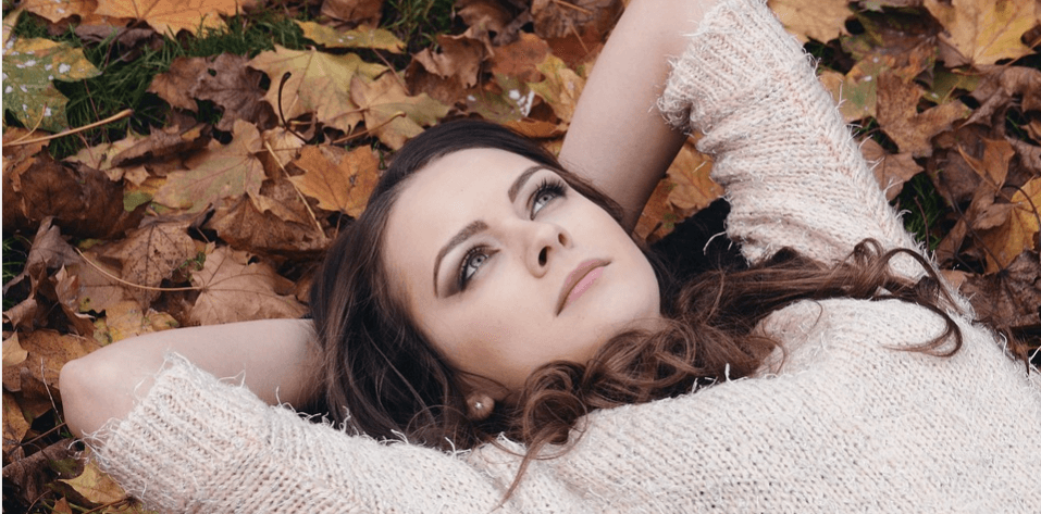 Woman lying in leaves with hands behind her head.