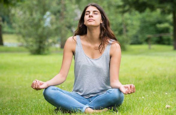 Girl on grass meditating.