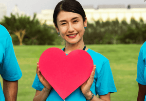 Woman smiling and holding a cutout heart.