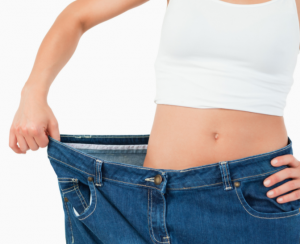 Woman holding trousers out to show weight loss.