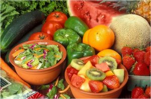 Bowl of salad and bowl of fruit surrounded with fruits and vegetables.