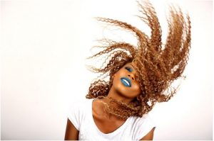 Girl with blue lips flipping curly hair.
