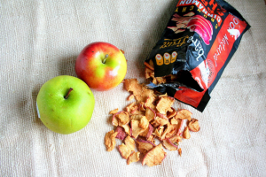 Open packet of Bare Snacks Apple Chips next to two apples.