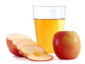 Glass of apple cider vinegar surrounded by chopped apple.