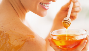 Smiling woman holding bowl of honey with dipper and lathering on skin.