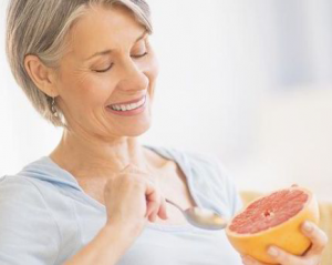 Woman eating half a grapefruit.