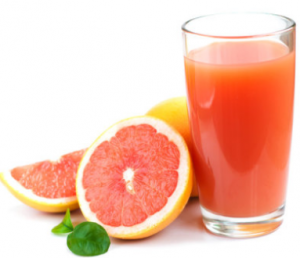 Glass of grapefruit juice with slice grapefruit leaning on it.