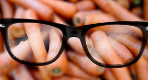 Pile of carrots with black rimmed glasses on them.