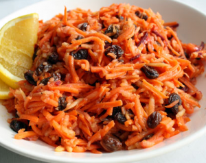 Grated carrot salad with raisins and a lemon slice.