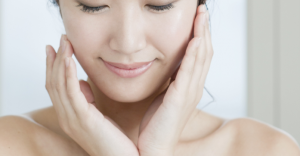 Woman rubbing serum on face.