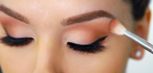 Close up of woman applying eyeshadow.