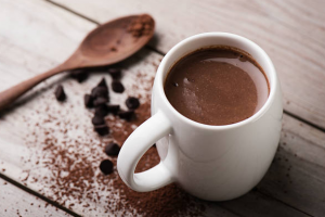 Hot chocolate in a mug with spoon and chocolate powder.