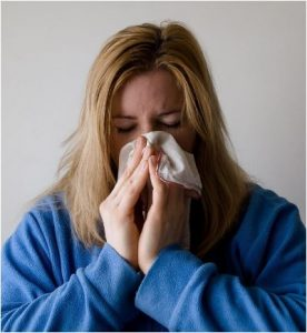 Woman sneezing into tissue.