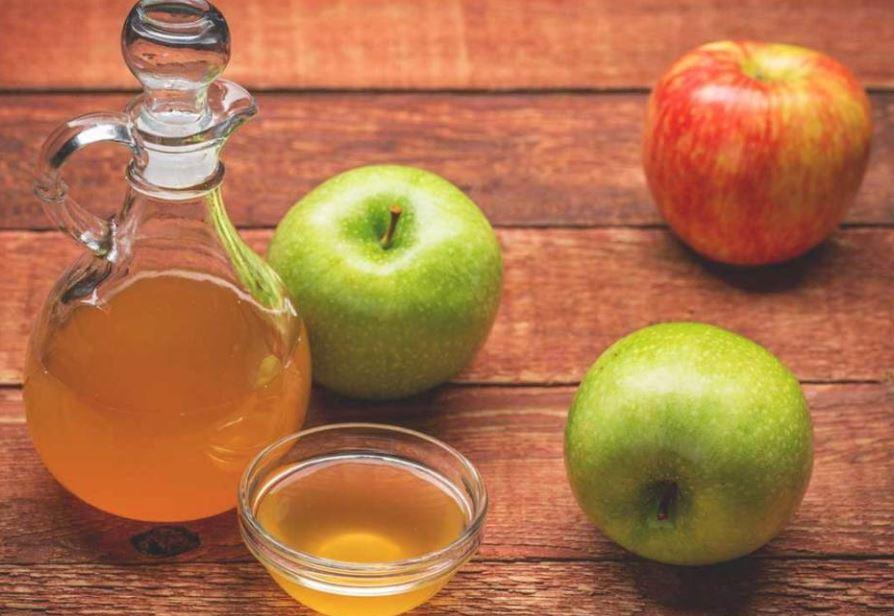 Apples and apple cider vinegar on table.