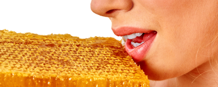 Woman bringing block of honeycomb to mouth.