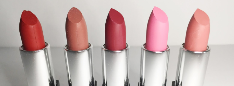 Assortment of lipsticks in a row with lids off.