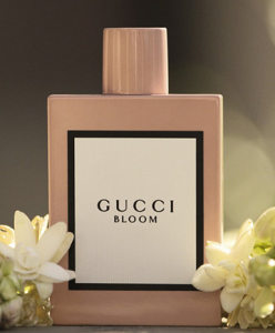 Gucci bloom perfume surrounded by flowers.
