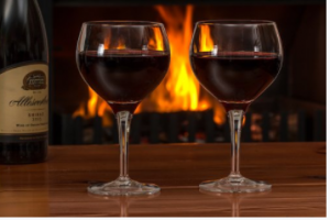 Two glasses of wine in front of fireplace.