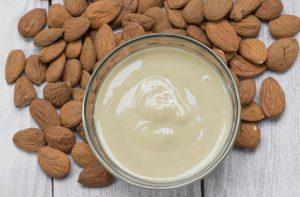 Almonds next to a bowl of almond yogurt.