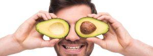 Man holding avocado halves over his eyes.