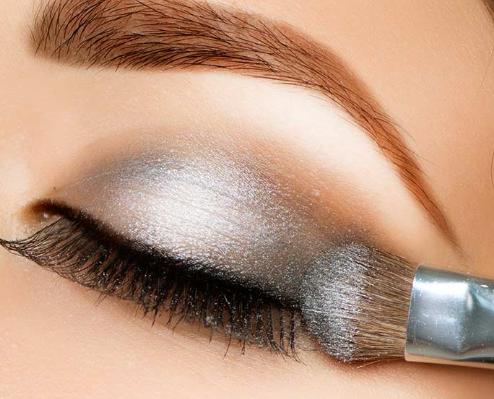Applying eyeshadow.