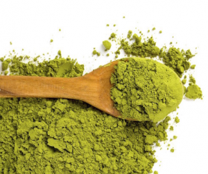 Matcha powder in wooden spoon.
