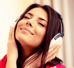 Girl smiling and wearing overear headphones.