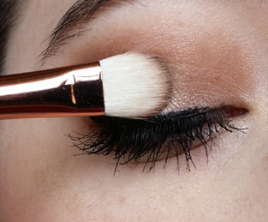 Woman applying eye shadow with brush.