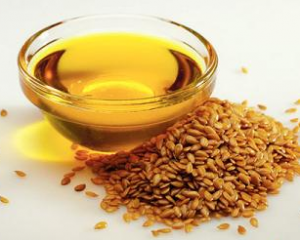 Flaxseed oil in bowl next to a pile of flax seeds.